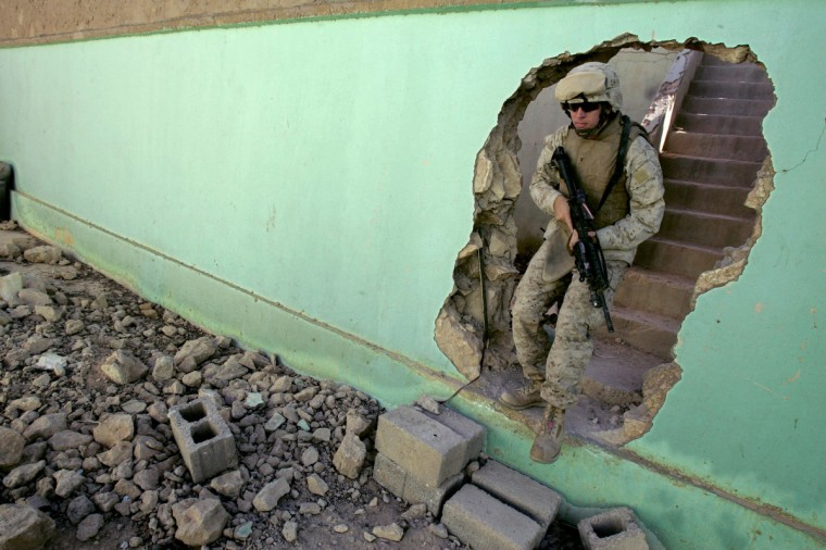 A US marine with 3/6 marines Lima company secures a position in the Iraqi-Syrian border town of Kusaiybah 27 October 2005 in western Iraq. US forces in Iraq have swelled to 161,000, their highest level since the US invasion in March 2003, a Pentagon spokesman said. The increase was due to overlapping troop rotations, said Lawrence DiRita, the chief Pentagon spokesman. (Patrick Baz/Getty Images)
