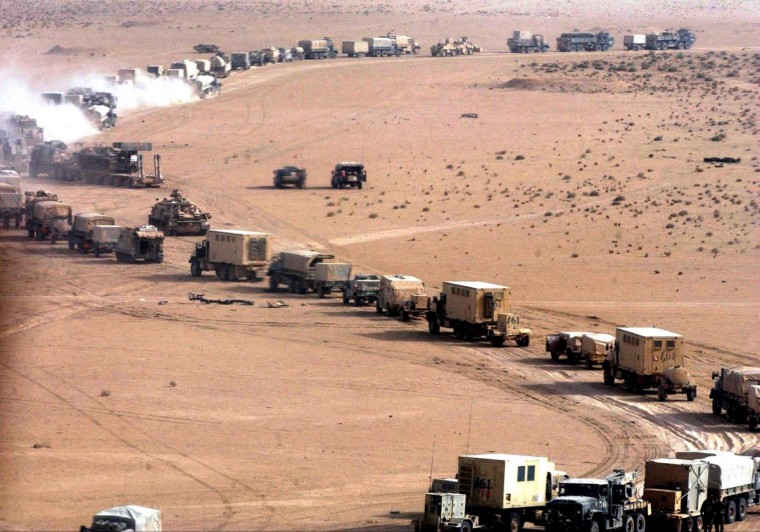 A long US military convoy is seen moving inside an unspecified area of southern Iraq 21 March 2003. US and British invasion forces were poised to capture the key Iraqi city of Basra as they swept through southern Iraq on day two of the war to topple President Saddam Hussein, taking several hundred soldiers prisoner. (Romeo Gacad/Getty Images)