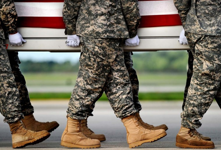 Army soldiers carry the flag-draped transfer case containing the remains of U.S. Army Maj. Thomas E. Kennedy, during a dignified transfer at Dover Air Force Base, on August 10, 2012 in Dover, Delaware. (Credit: Patrick Smith)