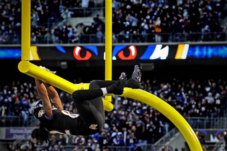 Wide receiver Torrey Smith #82 of the Baltimore Ravens hangs on the goal post after catching a touchdown pass during the first quarter against the New York Giants at M&T Bank Stadium on December 23, 2012 in Baltimore, Maryland. (Credit: Patrick Smith)