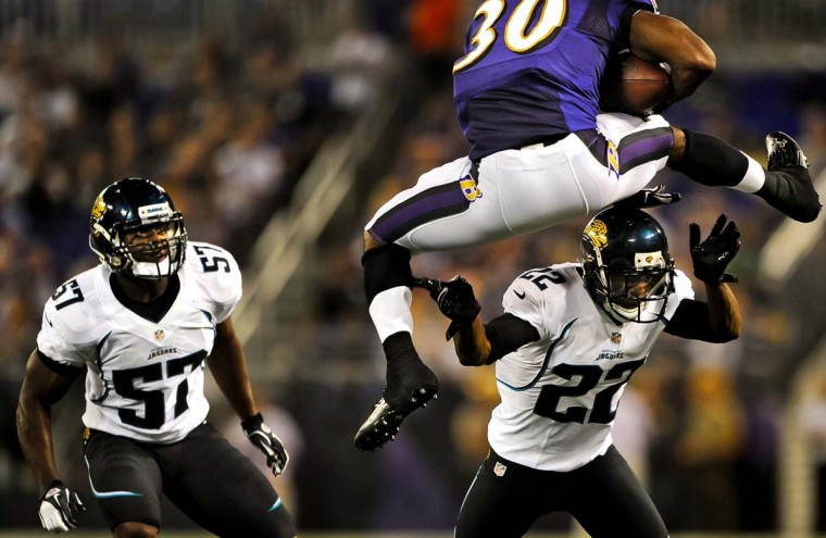 Running back Bernard Pierce #30 of the Baltimore Ravens leaps over cornerback Kevin Rutland #22 of the Jacksonville Jaguars as his teammate linebacker Julian Stanford #57 looks on during the third quarter at M&T Bank Stadium on August 23, 2012 in Baltimore, Maryland. (Credit: Patrick Smith)