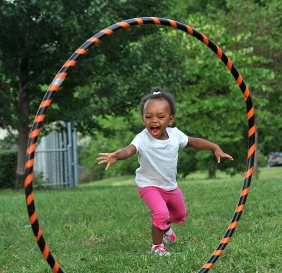 August 29, 2012: London Carry, 2, has fun with a hula hoop at the Druid Hill Farmers Market, where she came with her grandparents. (Amy Davis/Baltimore Sun)