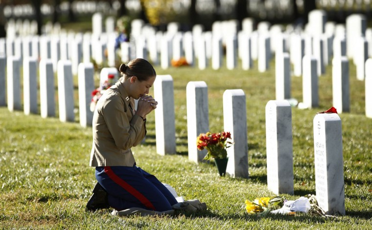 U.S. Marine Capt. Jill A. Leyden of Easton, Maryland, kneels at the grave of her friend Major Megan M. McClung at Arlington National Cemetery in Virginia on Veterans Day, November 11, 2010. McClung was killed during Operation Iraqi Freedom on December 6, 2006. Leyden and McClung served together in Iraq. (Kevin Lamarque/Reuters photo)