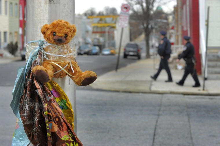 A teddy bear and deflated mylar balloons marking a spot of a recent murder are affixed to a street lamp at the corner of Payson St and Walbrook Avenue. (Karl Merton Ferron/Baltimore Sun)