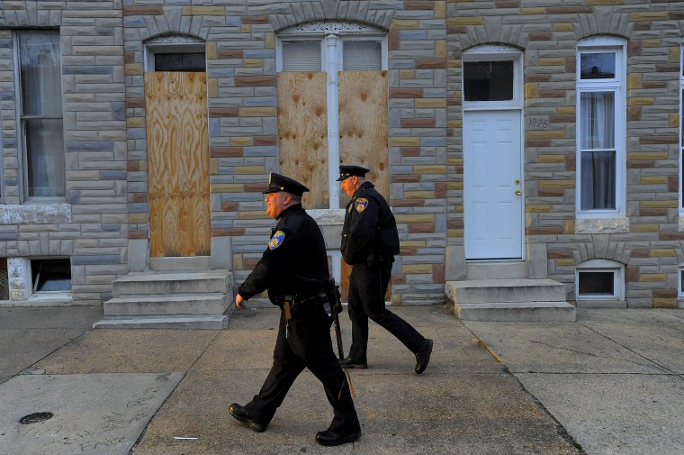 Baltimore City Police Detectives Michael Boyd (left) and Jim Mingle are illuminated by the sunset as they patrol along Walbrook Ave. between Fulton Av. and Payson St. (Karl Merton Ferron/Baltimore Sun)