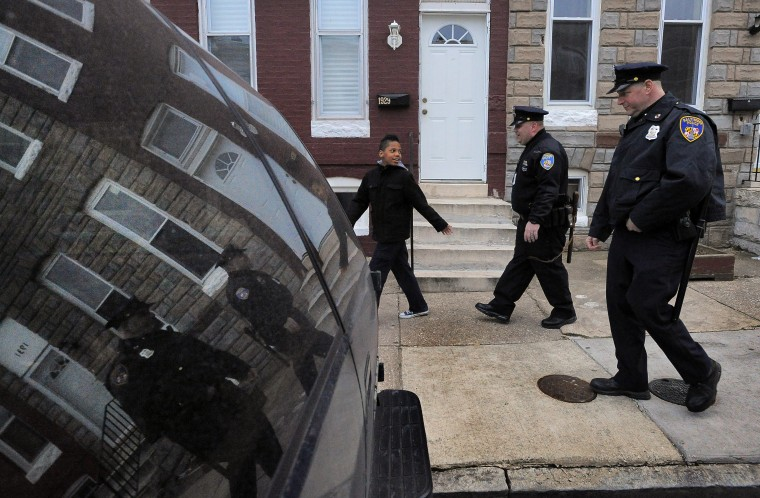 From left, Trévon Halstead, 12, keeps his interest in Baltimore City Police Detectives Michael Boyd and Jim Mingle as they patrol. (Karl Merton Ferron/Baltimore Sun)