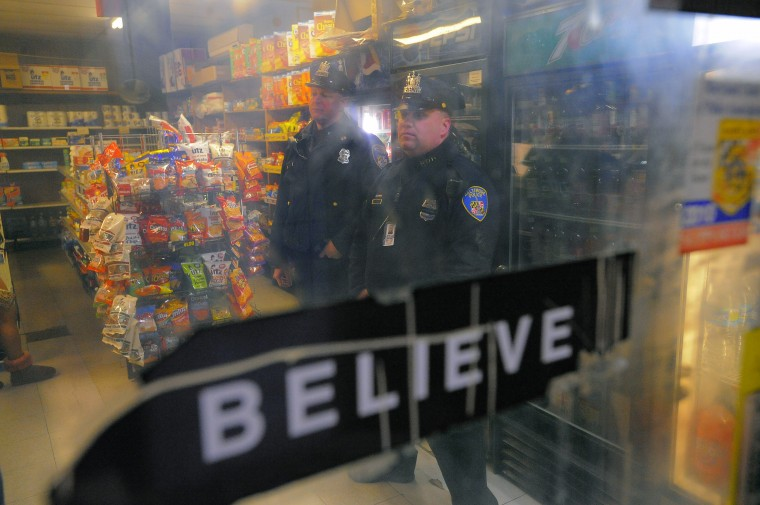 A worn and peeling bumper sticker touting an old Baltimore motto is affixed to clouded Plexiglas. Baltimore City Police Detectives Jim Mingle (left) and Michael Boyd, stand behind customers to check in with a store owner as they patrol along Walbrook Ave. between Fulton Av. and Payson St. in the city's Western District. (Karl Merton Ferron/Baltimore Sun)