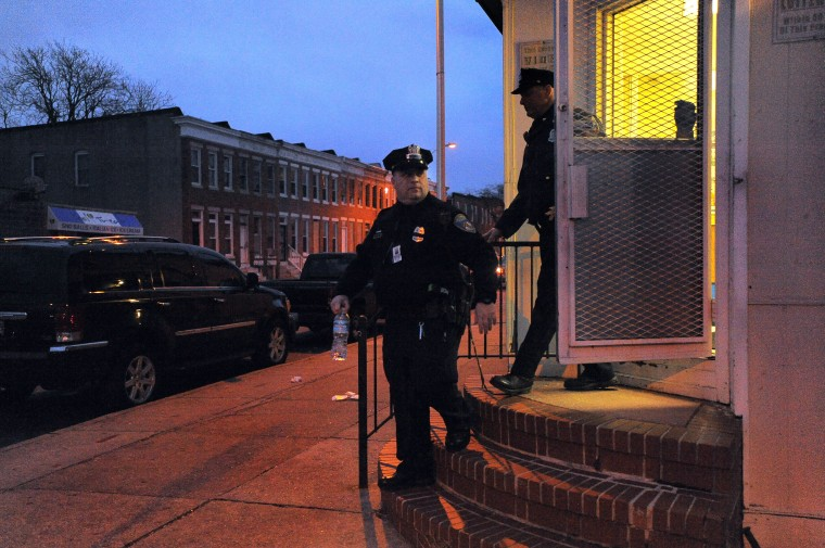 Baltimore City Police Detectives Michael Boyd (left) and Jim Mingle exit J & G Jamaican and American Carry Out as dusk settles during their patrol. (Karl Merton Ferron/Baltimore Sun)
