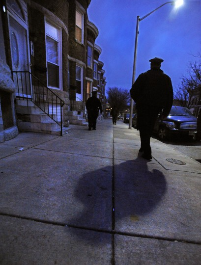 Baltimore City Police Detectives Jim Mingle casts a shadow on the sidewalk as he and Michael Boyd walk during their patrol. (Karl Merton Ferron/Baltimore Sun)