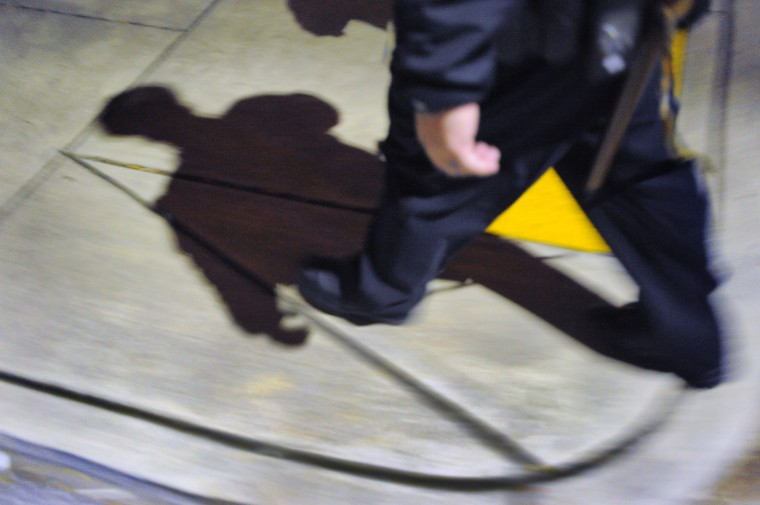 Baltimore City Police Detective Michael Boyd casts a shadow on the sidewalk while walking along Walbrook Ave. (Karl Merton Ferron/Baltimore Sun)