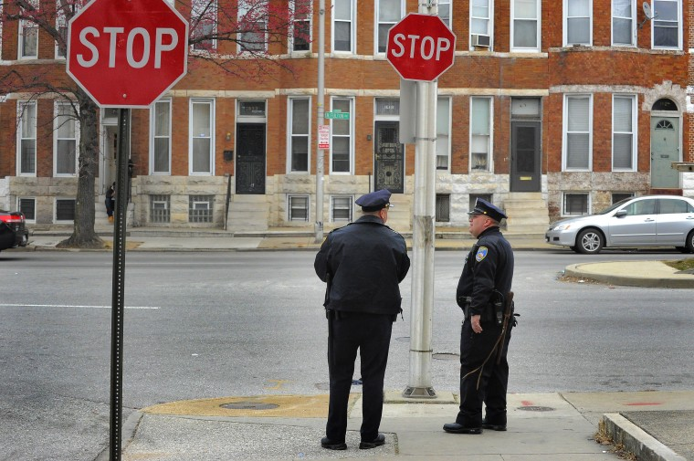 Baltimore City Police Detectives Michael Boyd and Jim Mingle stand on Fulton Avenue as they patrol along Walbrook Ave. in the city's Western District. (Karl Merton Ferron/Baltimore Sun)