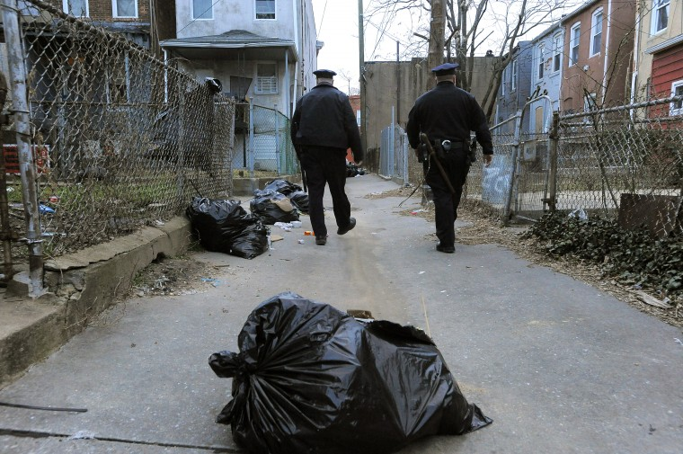 Baltimore City Police Detectives Michael Boyd and Jim Mingle walk around discarded bags of trash as they patrol in an alley behind Herbert St in the city's Western District. (Karl Merton Ferron/Baltimore Sun)