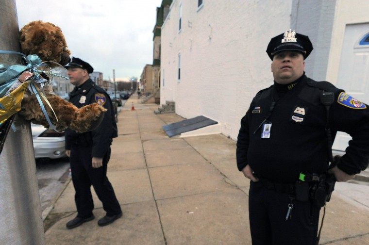 A teddy bear, placed to honor the victim of a past homicide still clings to a street lamp as Baltimore City Police Detectives Jim Mingle (left) and Michael Boyd patrol along Walbrook Ave. at Payson St. in the city's Western District. (Karl Merton Ferron/Baltimore Sun)