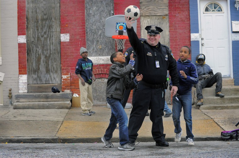 Tyrell Smith, 11 (background on left), watches Baltimore City Police Detective Michael Boyd take a moment to play street basketball, holding a soccer ball above neighborhood children Kevon Hansley, 10 (leather coat) and Tymique Goodman, 10 (blue sweats). (Karl Merton Ferron/Baltimore Sun)