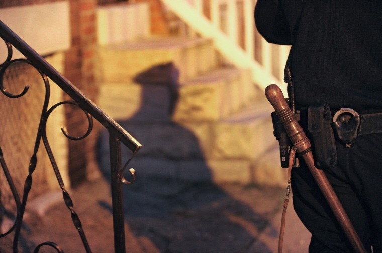 Baltimore City Police Detective Michael Boyd casts a shadow against the steps of a row house. (Karl Merton Ferron/Baltimore Sun)