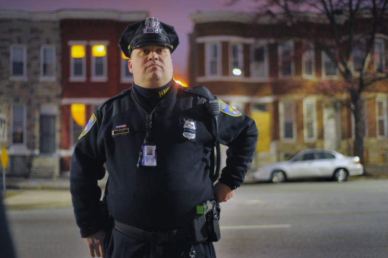 Baltimore City Police Detective Michael Boyd is illuminated by street light as he gazes up Walbrook Ave. between Fulton Av. and Payson St. in the city's Western District. (Karl Merton Ferron/Baltimore Sun)