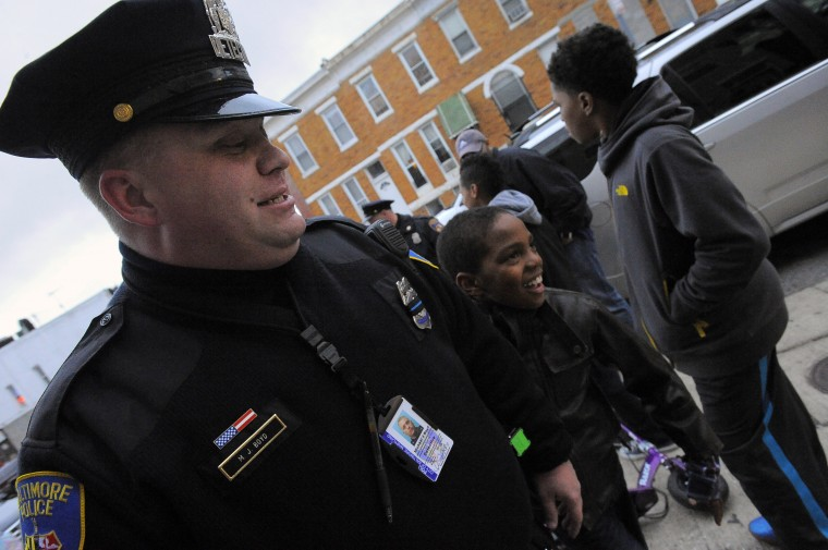 Neighborhood resident Kevon Hansley, 10 (leather coat) smiles while following Baltimore City Police Detective Michael Boyd as he finishes playing some street basketball and continues his patrol. (Karl Merton Ferron/Baltimore Sun)