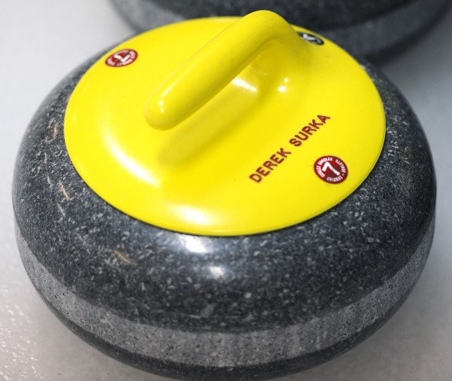 "Many stones have names on them. Derek Surka, the brothers said, is just ""really good"" at curling. (Jon Sham/BSMG)"