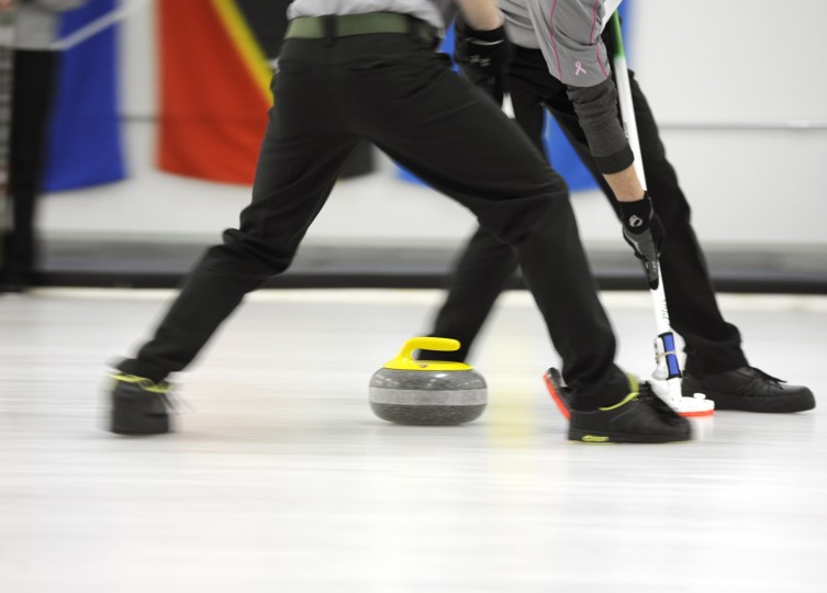 Caleb and Hunter sweep in front of a stone down the ice. The sweeping helps the stone travel further. (Jon Sham/BSMG)