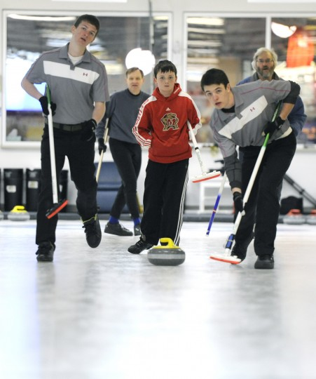 Eli Clawson, center, the youngest of the family, watches his stone travel down the ice while brothers Caleb, left, and Hunter prepare to sweep. (Jon Sham/BSMG)