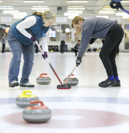 Marsha Allen, left, of Columbia, and John Warshawsky, of Bethesda, sweep in front of a stone during a friend match with the Clawson family. (Jon Sham/BSMG)
