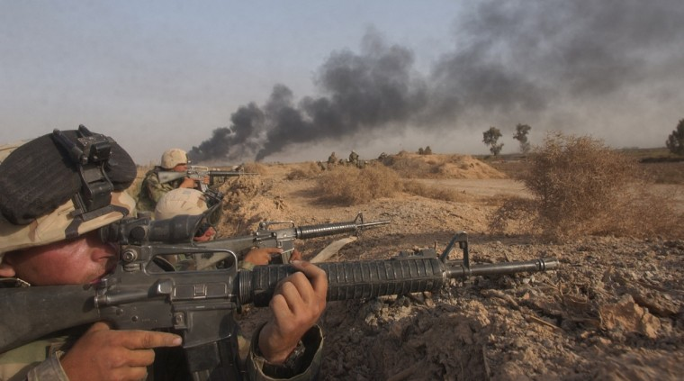 Al Aziziyah, Iraq -- April 2, 2003 -- The Marines of India company 3/5 take positions to cover a field of fire as other units swept through the field. The battle that day became a costly one for India company when one marine died and at least two others were wounded. (John Makely/Baltimore Sun)