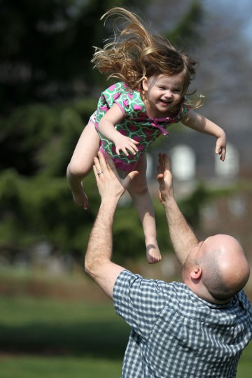 Steve Sherman of Homeland catches his daughter Scarlett Sherman, 3, while playing outside at Sherwood Gardens in Baltimore, MD on Saturday, March 17, 2012. (Jen Rynda, The Baltimore Sun)