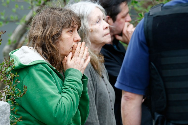 A woman reacts while being questioned by the FBI and other law enforcement agencies on April 19, 2013 near the home of suspect #2 on Norfolk Street in Cambridge, Massachusetts. Earlier, a Massachusetts Institute of Technology campus police officer was shot and killed late Thursday night at the school's campus in Cambridge. A short time later, police reported exchanging gunfire with alleged carjackers in Watertown, a city near Cambridge. According to reports, one suspect has been killed during a car chase and the police are seeking another - believed to be the same person (known as Suspect Two) wanted in connection with the deadly bombing at the Boston Marathon earlier this week. Police have confirmed that the dead assailant is Suspect One from the recently released marathon bombing photographs. (Jared Wickerham/Getty Images)