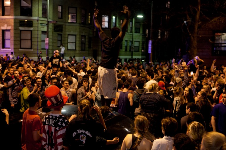 An the estimated 200 people pour onto Hemingway Street in the Fenway neighborhood to celebrate after the announcement earlier of the capture of the second Boston Martathon bombing suspect celebrate April 19, 2013 in Boston, Massachusetts. A manhunt for Dzhokhar A. Tsarnaev, 19, ended this evening with his capture on a boat parked on a residential property in Watertown, Massachusetts. His brother Tamerlan Tsarnaev, 26, the other suspect, was shot and killed by police early this morning after a car chase and shootout with police. The bombing killed three people and wounded at least 170. (Photo by Kayana Szymczak/Getty Images)