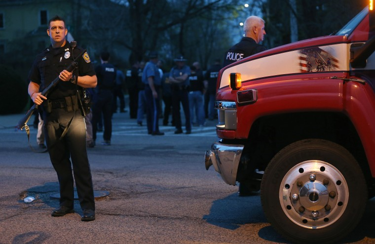 A police officer keeps watch after responding to a reported shooting next to a small 9/11 tribute painted on a truck on April 19, 2013 in Watertown, Massachusetts. After a car chase and shoot out with police, one suspect in the Boston Marathon bombing, Tamerlan Tsarnaev, 26, was shot and killed by police early morning April 19, and a manhunt is underway for his brother and second suspect, 19-year-old suspect Dzhokhar A. Tsarnaev. The two men, reportedly Chechen of origin, are suspects in the bombings at the Boston Marathon on April 15, that killed three people and wounded at least 170. (Photo by Mario Tama/Getty Images)