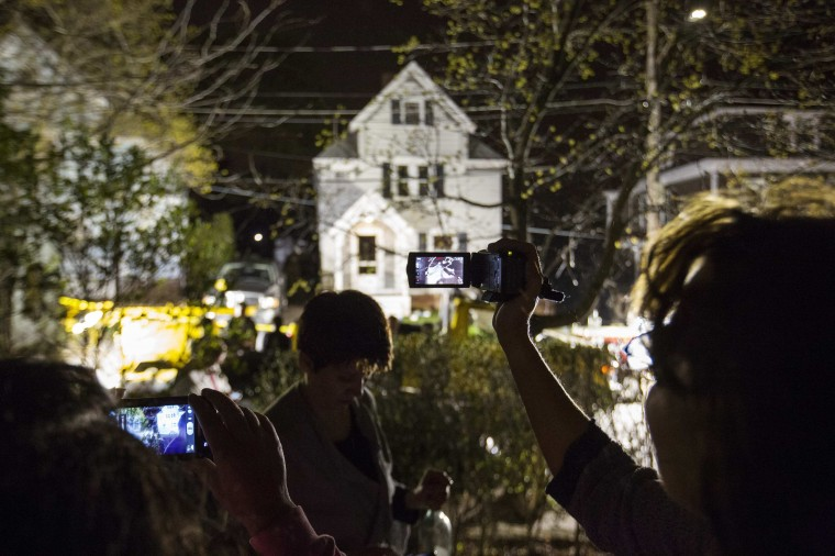 Neighbors use cameras to record images of the boat at 67 Franklin St. where Dzhokhar Tsarnaev, the surviving suspect in the Boston Marathon bombings, was hiding inside in Watertown, Massachusetts, April 19, 2013. Boston Police said on Friday they have taken custody of the second suspect, Dzhokhar Tsarnaev, and are sweeping the suburban Boston neighborhood where he was captured after a massive manhunt. REUTERS/Lucas Jackson