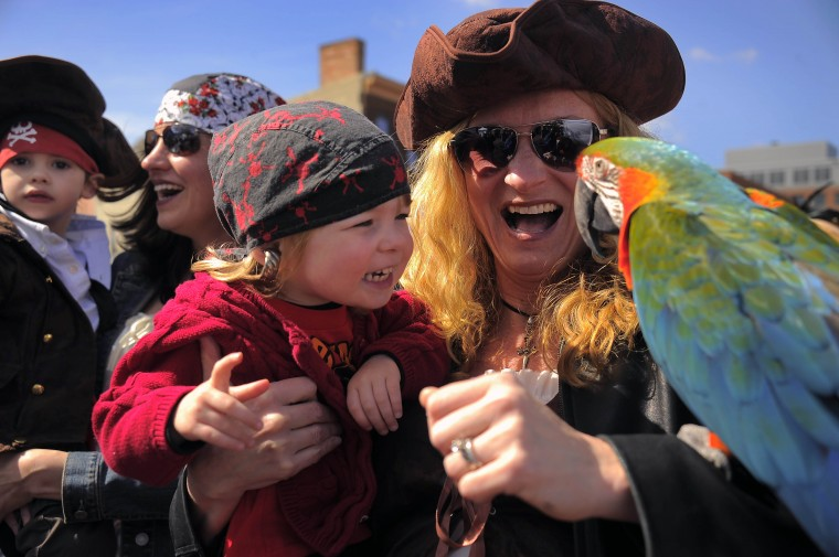 Suzanne De Kleine of Saylorsburg, PA holds her son Robert (left) as Joanie Ziemski of Owings Mills holds her daughter Mary Ziemski, 2, who looks at Fiametta, owned by Yvonne Lanting of the Baltimore Bird Fanciers during the 2013 Privateer Festival at Fells Point Saturday, Apr. 20, 2013. (Karl Merton Ferron/Baltimore Sun Staff)
