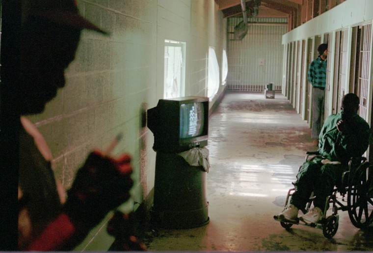 In 1994, correctional officer Mallory Bland, silhouetted on the left, keeps an eye on Section B of the Baltimore City Detention Center as a wheelchair bound detainee watches a TV propped on a trash can. (Robert K. Hamilton/ Baltimore Sun)
