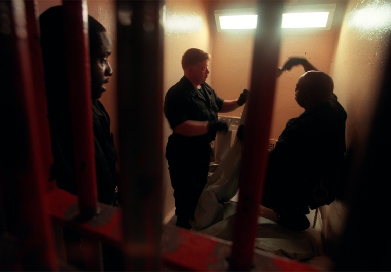 Corrections officers Anthony Ramsey, Steven Hall, and Donald Anthony search a cell in the Baltimore City Detention Center in 1999. (Lloyd Fox/Baltimore Sun)