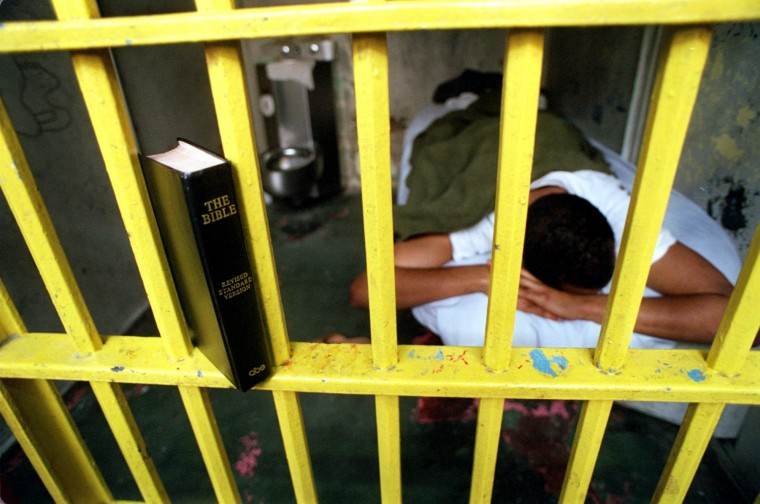 In 2000, a detainee on the Segregation Unit uses the cell bars as a bookshelf. (Jed Kirschbaum/Baltimore Sun)