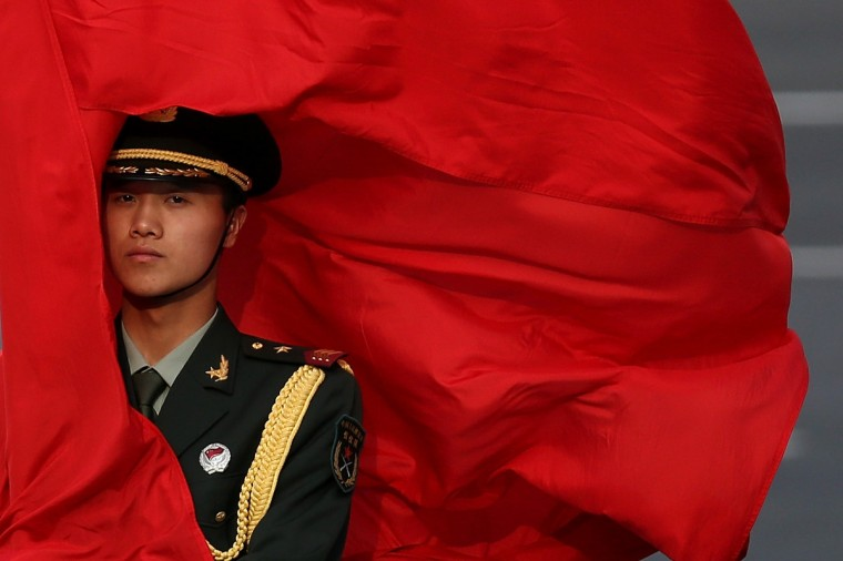 The wind blows a red flag onto the face of an honor guard before a welcome ceremony for Australia's Prime Minister Julia Gillard outside the Great Hall of the People in Beijing, China. At the invitation of Chinese Premier Li Keqiang, Australian Prime Minister Julia Gillard will pay an official visit to China after the Boao Forum for Asia Annual Conference 2013. (Feng Li/Getty Images)