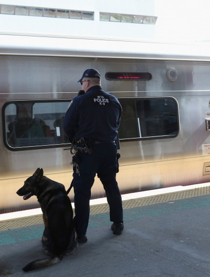 A police officer with his K-9 companion keeps guard as a Long Island Rail Road train from New York City arrives at the station on April 15, 2013 in Hicksville, New York. According to reports, at least two people were killed and 28 injured in two blasts near the finish of the Boston Marathon on Monday. (Bruce Bennett/Getty Images)