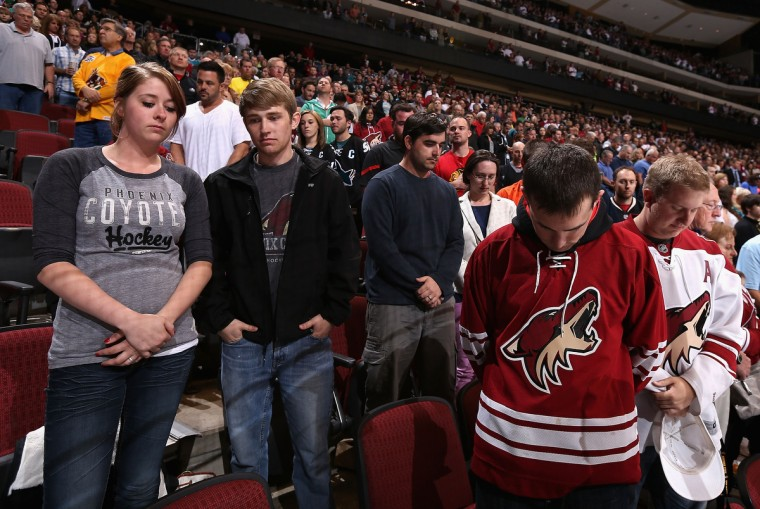 Fans take a moment of silence in honor of the Boston Marathon explosions before the NHL game between the Phoenix Coyotes and the San Jose Sharks at Jobing.com Arena on April 15, 2013 in Glendale, Arizona. The Sharks defeated the Coyotes 4-0. ( Christian Petersen/Getty Images)
