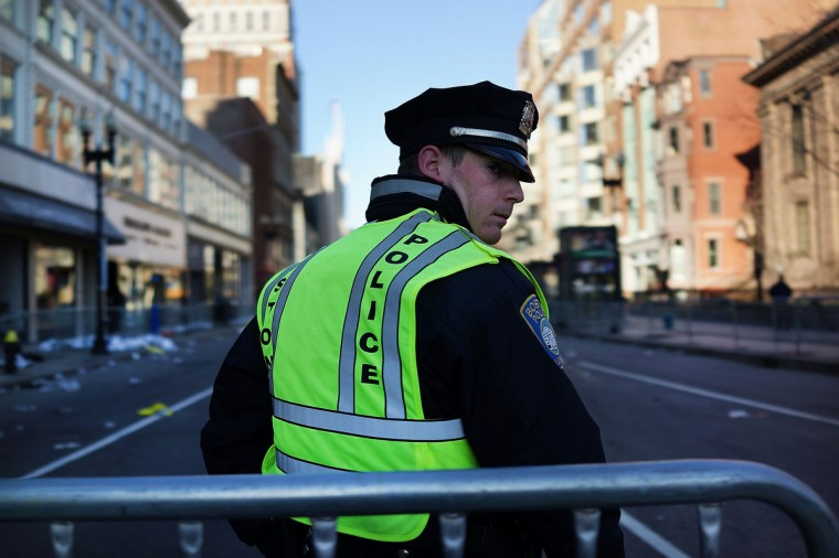 A Boston police officer stands near the scene of a twin bombing at the Boston Marathon on April 16, 2013 in Boston, Massachusetts. The twin bombings, which occurred near the marathon finish line, resulted in the deaths of three people while hospitalizing at least 128. The bombings at the 116-year-old Boston race, resulted in heightened security across the nation with cancellations of many professional sporting events as authorities search for a motive to the violence. (Spencer Platt/Getty Images)