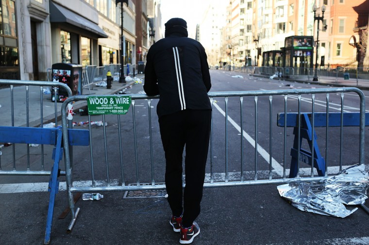 A runner stands at a security gate near the scene of a twin bombing at the Boston Marathon on April 16, 2013 in Boston, Massachusetts. The twin bombings, which occurred near the marathon finish line, resulted in the deaths of three people while hospitalizing at least 128. The bombings at the 116-year-old Boston race, resulted in heightened security across the nation with cancellations of many professional sporting events as authorities search for a motive to the violence. (Spencer Platt/Getty Images)