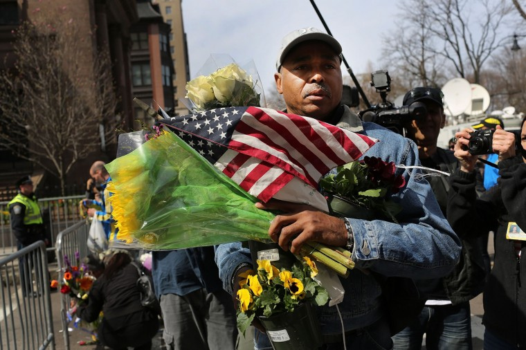A man carries flowers and flags to a memorial for victims blocks away from the scene of yesterday's bombing attack at the Boston Marathon on April 16, 2013 in Boston, Massachusetts. The twin bombings, which occurred near the marathon finish line, resulted in the deaths of three people while hospitalizing at least 128. (Spencer Platt/Getty Images)