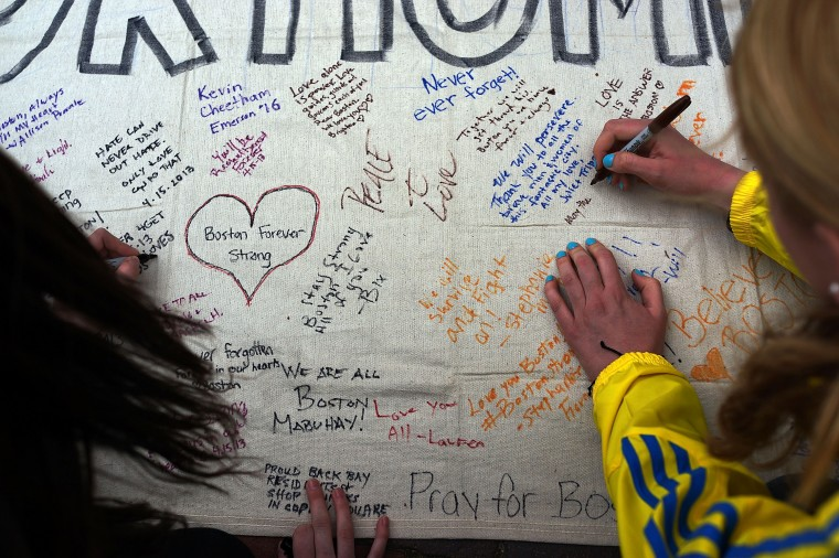 People write messages on a memorial canvas during a vigil for victims of the Boston Marathon bombings at Boston Commons on April 16, 2013 in Boston, Massachusetts. The twin bombings, which occurred near the marathon finish line, resulted in the deaths of three people while hospitalizing at least 140. The bombings at the 116-year-old Boston race, resulted in heightened security across the nation with cancellations of many professional sporting events as authorities search for a motive to the violence. (Spencer Platt/Getty Images)