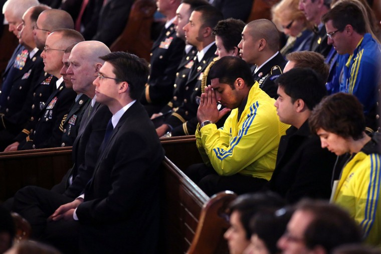 "Runners pray at an interfaith prayer service for victims of the Boston Marathon attack titled ""Healing Our City,"" and attended by President Barack Obama and first lady Michelle Obama at the Cathedral of the Holy Cross on April 18, 2013 in Boston, Massachusetts. (Spencer Platt/Getty Images)"