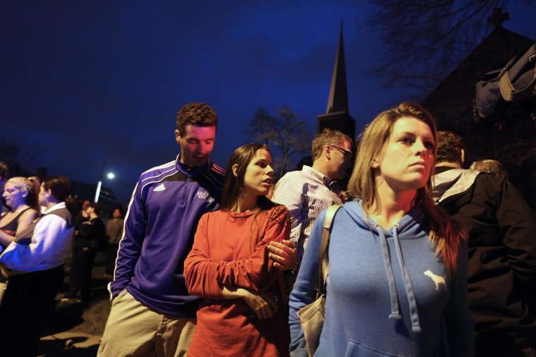 People react while watching police respond to a reported shooting on April 19, 2013 in Watertown, Massachusetts. After a car chase and shoot out with police, one suspect in the Boston Marathon bombing, Tamerlan Tsarnaev, 26, was shot and killed by police early morning April 19, and a manhunt is underway for his brother and second suspect, 19-year-old suspect Dzhokhar A. Tsarnaev. The two men, reportedly Chechen of origin, are suspects in the bombings at the Boston Marathon on April 15, that killed three people and wounded at least 170. (Mario Tama/Getty Images)