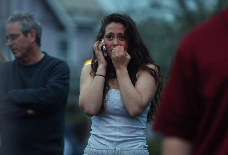 Resident Rosie Meyer (C), who said she heard gunshots, reacts while watching police respond on April 19, 2013 in Watertown, Massachusetts. After a car chase and shoot out with police, one suspect in the Boston Marathon bombing, Tamerlan Tsarnaev, 26, was shot and killed by police early morning April 19, and a manhunt is underway for his brother and second suspect, 19-year-old suspect Dzhokhar A. Tsarnaev. The two men, reportedly Chechen of origin, are suspects in the bombings at the Boston Marathon on April 15, that killed three people and wounded at least 170. (Mario Tama/Getty Images)