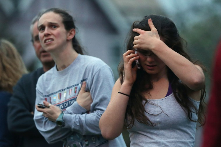 People react while watching police respond to reported gunfire on April 19, 2013 in Watertown, Massachusetts. After a car chase and shoot out with police, one suspect in the Boston Marathon bombing, Tamerlan Tsarnaev, 26, was shot and killed by police early morning April 19, and a manhunt is underway for his brother and second suspect, 19-year-old suspect Dzhokhar A. Tsarnaev. The two men, reportedly Chechen of origin, are suspects in the bombings at the Boston Marathon on April 15, that killed three people and wounded at least 170. (Mario Tama/Getty Images)