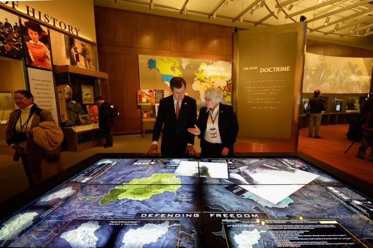 Docent Patricia Flynn shows president of Southern Methodist University R. Gerald Turner the interactive table of conflicts in the Middle East called Defending Freedom at the George W. Bush Presidential Center on the campus of Southern Methodist University on April 24, 2013 in Dallas, Texas. Dedication of the George W. Bush Presidential Library is to take place on April 25 with all five living U.S. Presidents in attendance. ((Kevork Djansezian/Getty Images)