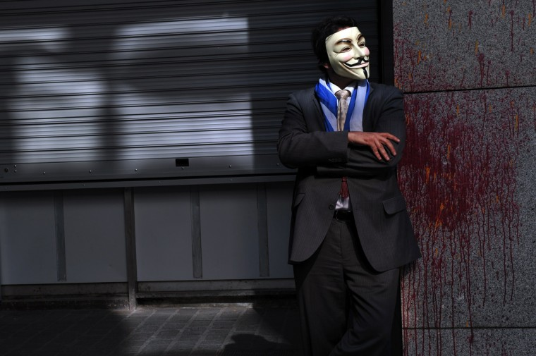 A protester wearing a Guy Fawkes mask stands outside the Finance Ministry in Athens, as 'Independent Greeks' party members and supporters take part in a protest as they waited for the arrival of the EU-IMF-ECB troika, whose meeting was finally rescheduled. EU and IMF auditors are to meet Greek Finance Minister Yannis Stournaras later today, as they resume an audit suspended days before the eruption of the banking crisis in Cyprus.(Louisa Gouliamaki/Getty Images)