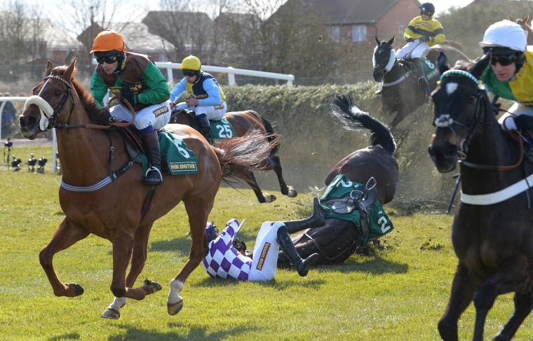 Horse 'Bold Addition' ridden by Steven Clements (C) falls at Beechers Brook during the Fox Hunters Steeple Chase on the opening day of the Grand National Meeting horse racing event at Aintree Racecourse in Liverpool, north-west England. (Andrew Yates/Getty Images)