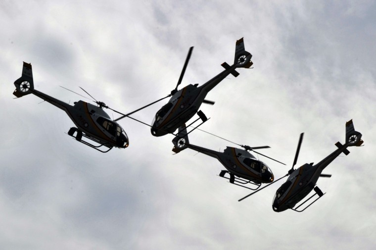 Helicopter Dynamic Pegassus perform an air show during a parade of the 67th anniversary commemoration of the Indonesian Air Force at an airbase in Jakarta. The Indonesian Air Force has more than 30,000 personnel equipped with more than 100 combat aircrafts, including Su-27 and Su-30. (Bay Ismoyo/Getty Images)